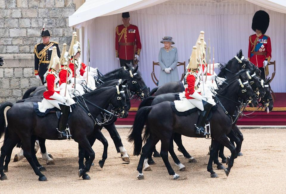 <p>The Queen watching as members of the military ride by on horseback at Trooping the Colour 2021. </p>