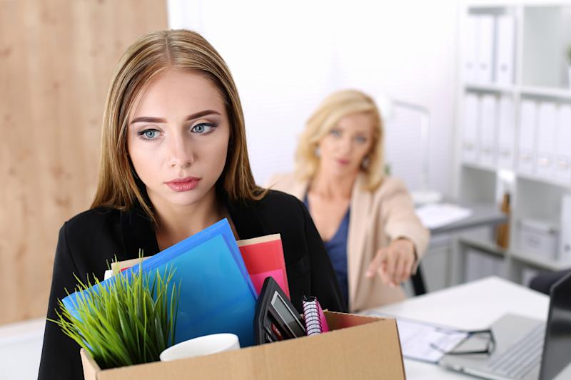 Woman with sad expression carrying cardboard box of office supplies while a seated woman behind her looks on