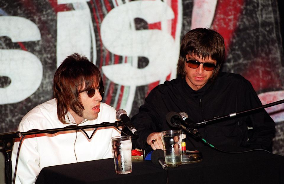 Liam (L) and Noel Gallagher from the band Oasis at a press conference in London to announce that bass player Paul 'Guigsy' McGuigan has quit the band - a little over two weeks after guitarist Paul 'Bonehead' Arthurs did the same.   (Photo by Fiona Hanson - PA Images/PA Images via Getty Images)