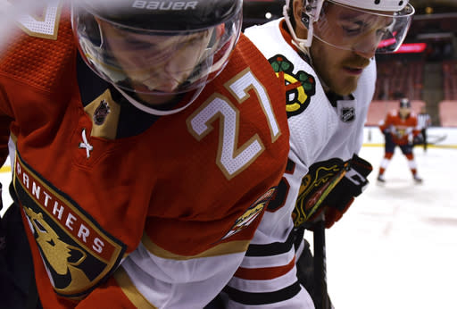 Florida Panthers center Eetu Luostarinen (27) and Chicago Blackhawks right wing Andrew Shaw (65) battle for the puck in the second period of an NHL hockey game Sunday, Jan. 17, 2021, in Sunrise, Fla. (AP Photo/Jim Rassol)