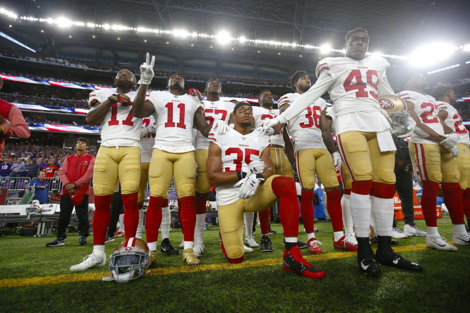 Eric Reid #35 of the San Francisco 49ers kneels during the anthem as teammates gather around him in support prior to the game against the Minnesota Vikings at U.S. Bank Stadium on August 27, 2017 in Minneapolis, Minnesota. The Vikings defeated the 49ers 32-31. (Photo by Michael Zagaris/San Francisco 49ers/Getty Images)