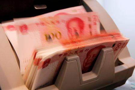 Chinese 100 yuan banknotes are seen in a counting machine while a clerk counts them at a branch of a commercial bank in Beijing, China, March 30, 2016. REUTERS/Kim Kyung-Hoon/Files