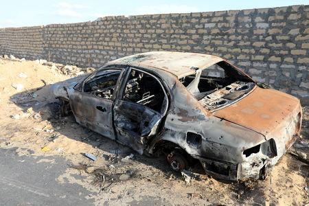 A damaged car is seen during the fight between the armed forces allied to internationally recognised government and armed group in Tripoli
