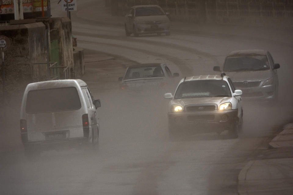 Vehicles drive on the main Black Rock road, covered with ash coming from the St. Vincent eruption of La Soufriere volcano, on the outskirts of Bridgetown, Barbados, Sunday, April 11, 2021. (AP Photo/Chris Brandis)