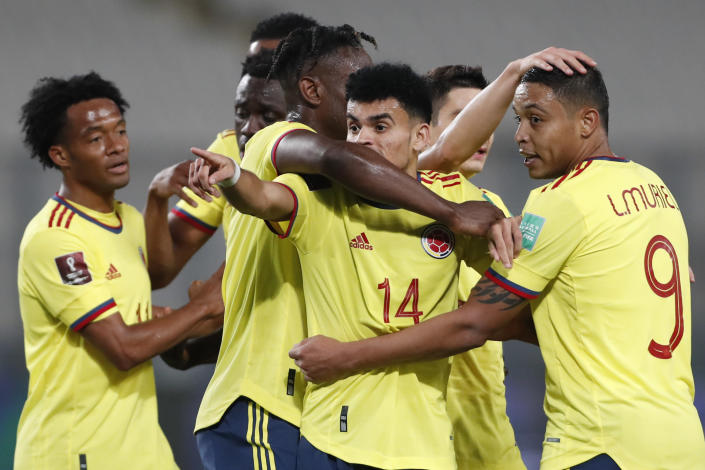 Colombia's Luis Diaz (14) celebrates scoring his side's third goal against Peru during a qualifying soccer match for the FIFA World Cup Qatar 2022 at the National stadium in Lima, Peru, Thursday, June 3, 2021. (Paolo Aguilar/Pool via AP)