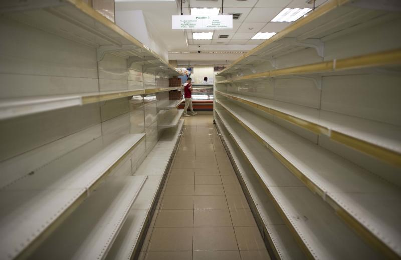 Empty shelves stand in a supermarket in Caracas, Venezuela, Friday, March 23, 2018. Venezuelan President Nicolas Maduro announced Thursday he's tackling the country's staggering inflation by lopping three zeros off the increasingly worthless bolivar currency. He said the new banknotes should begin circulating in early June. (AP Photo/Ariana Cubillos)