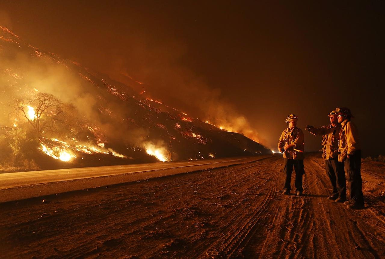 <p>Firefighters monitor a section of the Thomas Fire along the 101 freeway on December 7, 2017 north of Ventura, Calif. (Photo: Mario Tama/Getty Images) </p>