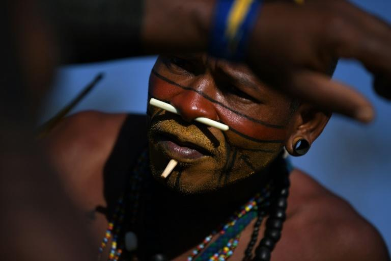 An indigenous man from the Pataxo tribe paints the body of a fellow demonstrator at a protest camp in Brasilia, Brazil on August 25, 2021