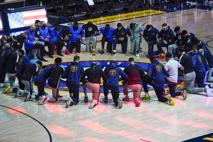 """FILE - Members of the Denver Nuggets and the Dallas Mavericks lock arms and take a knee during the national anthem before an NBA basketball game in Denver, in this Thursday, Jan. 7, 2021, file photo. The NBA said Wednesday, Feb. 10, 2021, the national anthem will be played in arenas """"in keeping with longstanding league policy"""" after Dallas Mavericks owner Mark Cuban revealed he had decided not to play it before his team's home games this season. (AP Photo/Jack Dempsey, File)"""