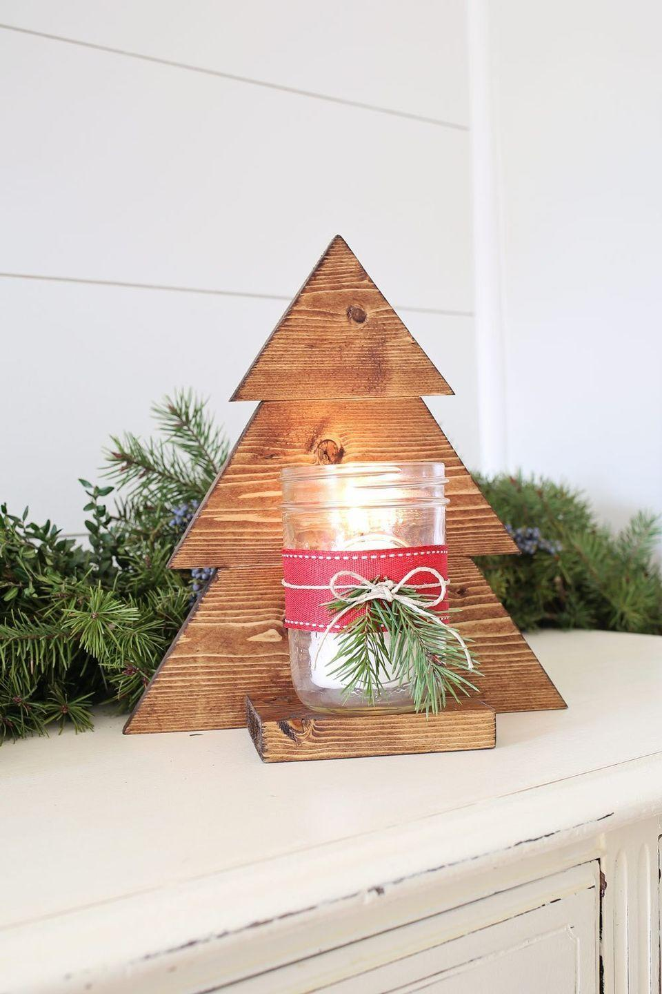 """<p>Whether you want to hang it on your wall or set it on your <a href=""""https://www.countryliving.com/home-design/decorating-ideas/g1571/holiday-mantels/"""" rel=""""nofollow noopener"""" target=""""_blank"""" data-ylk=""""slk:mantel"""" class=""""link rapid-noclick-resp"""">mantel</a>, this Christmas tree sconce will look great anywhere you put it. If you want, you can even make it into a beautiful <a href=""""https://www.countryliving.com/shopping/g4758/stocking-holders/"""" rel=""""nofollow noopener"""" target=""""_blank"""" data-ylk=""""slk:stocking holder"""" class=""""link rapid-noclick-resp"""">stocking holder</a>.</p><p><strong>Get the tutorial from <a href=""""https://angelamariemade.com/diy-wood-christmas-tree-mason-jar-sconce/"""" rel=""""nofollow noopener"""" target=""""_blank"""" data-ylk=""""slk:Angela Marie Made"""" class=""""link rapid-noclick-resp"""">Angela Marie Made</a>.</strong></p><p><strong><a class=""""link rapid-noclick-resp"""" href=""""https://www.amazon.com/Howard-RF3008-Restor-Finish-8-Ounce/dp/B003DNRH2A/?tag=syn-yahoo-20&ascsubtag=%5Bartid%7C10050.g.2132%5Bsrc%7Cyahoo-us"""" rel=""""nofollow noopener"""" target=""""_blank"""" data-ylk=""""slk:SHOP WOOD FINISH"""">SHOP WOOD FINISH</a><br></strong></p>"""