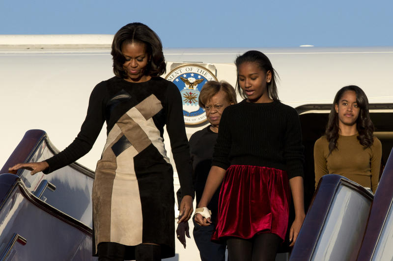 U.S. First Lady Michelle Obama, front left, her daughters Sasha, front right, Malia, right in the back, and Michelle Obama's mother Marian Robinson, left in the back, arrive at Capital International Airport in Beijing, China, Thursday, March 20, 2014. Michelle Obama has arrived in Beijing with her mother and daughters to kick off a seven-day, three-city tour where she will focus on education and cultural exchange. (AP Photo/Alexander F. Yuan, Pool)