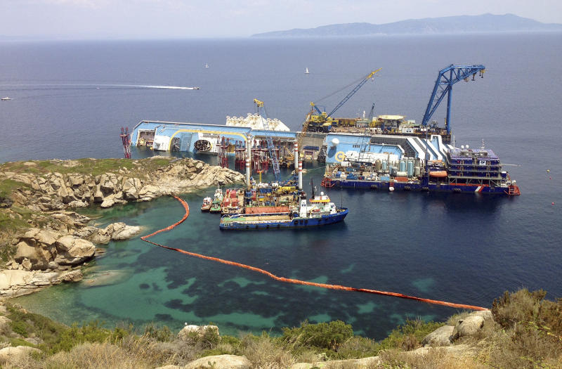 The Costa Concordia cruise ship lies on its side in the waters of the Tuscan island of Giglio, Italy, Monday, July 8, 2013. The luxury cruise ship ran aground off the coast of Tuscany on Jan 13, 2012, sending water pouring in through a 160-foot (50-meter) gash in the hull and forcing the evacuation of some 4,200 people from the listing vessel early. (AP Photo Paolo Santalucia)