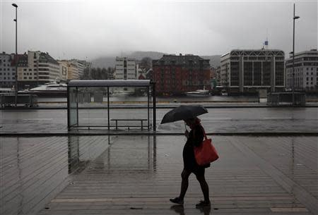 A woman walks with an umbrella during light rain near the marina in downtown Bergen, southwestern Norway, in this March 20, 2012 file photo. REUTERS/Stoyan Nenov/Files