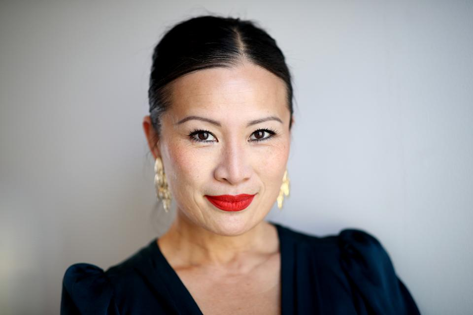 Poh Ling Yeow wears a navy dress, gold earrings and red lipstick at the L'Oréal Paris Revitalift Retinol Launch on May 26, 2021 in Sydney, Australia