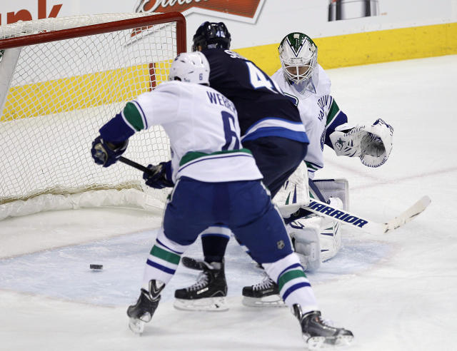 Winnipeg Jets' Devin Setoguchi (40)scores on Vancouver Canucks goaltender Eddie Lack (31) as Canucks' Yannick Weber (6) defends during the first period of an NHL hockey game in Winnipeg, Manitoba, on Friday, Jan. 31, 2014. (AP Photo/The Canadian Press, John Woods)