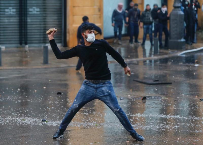 A demonstrator throws a stone during a protest against a ruling elite accused of steering Lebanon towards economic crisis in Beirut