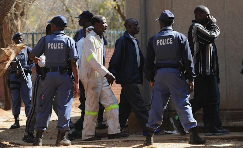 Police keep an eye on arrested mineworkers as they arrive at a court in Ga-Rankuwa, north of Pretoria, South Africa, Monday Aug 20, 2012. The miners are among 259 expected to be charged with public violence at the Lonmin Platinum Mine where police shot and killed 34 striking workers last week. (AP Photo)
