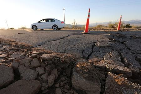 A car passes over a fissure that opened on a highway during a powerful earthquake that struck Southern California, near the city of Ridgecrest