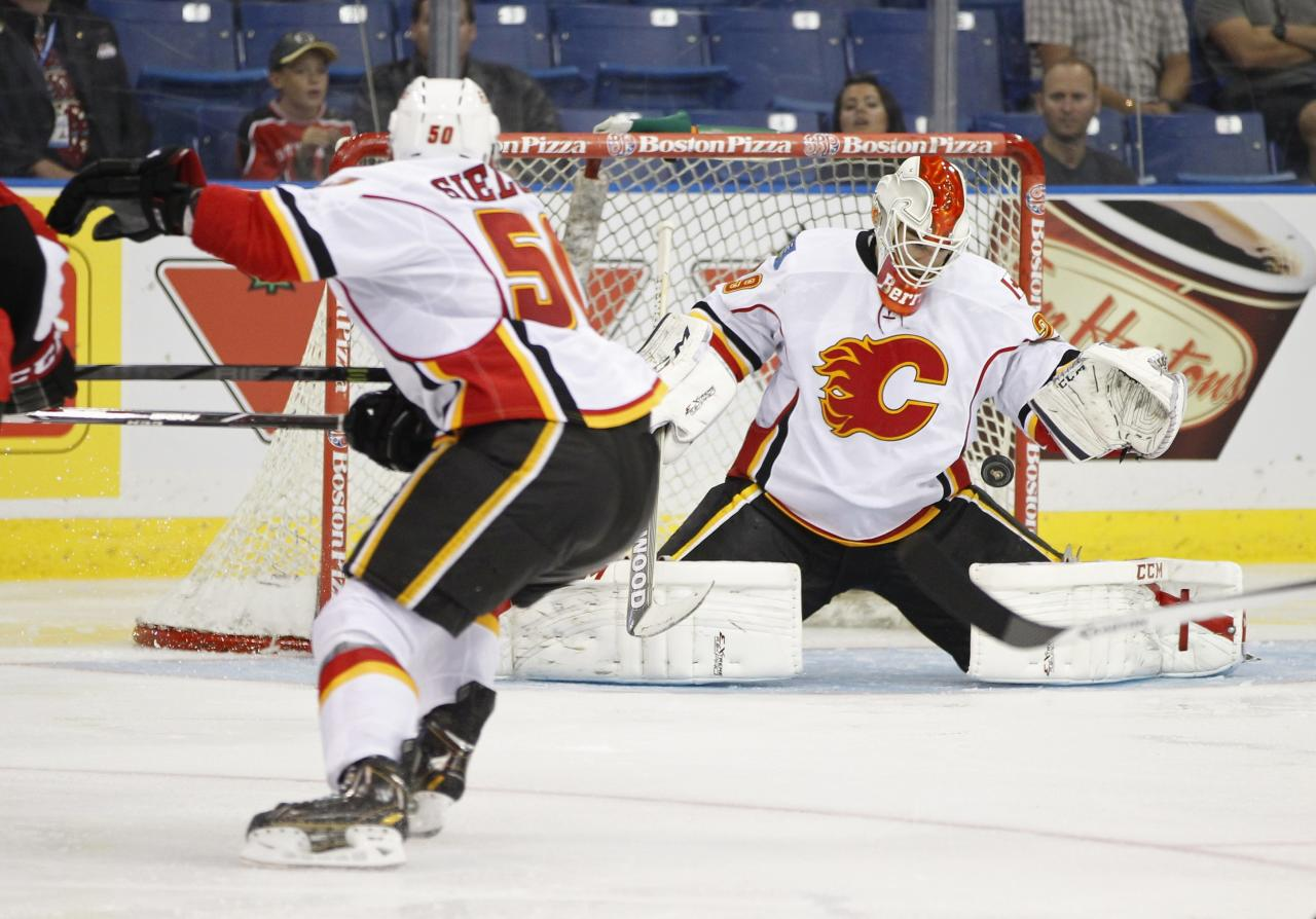 Calgary Flames goalie Reto Berra makes a save while playing against the Ottawa Senators during the second period of their NHL hockey game in Saskatoon, Saskatchewan September 16, 2013. REUTERS/David Stobbe (CANADA - Tags: SPORT ICE HOCKEY)