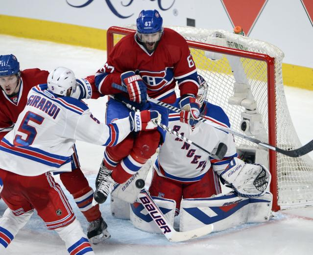 Montreal Canadiens' Max Pacioretty, center, screens New York Rangers goalie Cam Talbot as Rangers' Dan Girardi defends and Canadiens' Brendan Gallagher, right, skates to the top of the crease during the second period of Game 5 of the NHL hockey Stanley Cup playoffs Eastern Conference finals, Tuesday, May 27, 2014, in Montreal. (AP Photo/The Canadian Press, Ryan Remiorz)