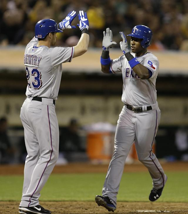Texas Rangers' Jurickson Profar, right, is congratulated by Craig Gentry after Profar hit a two-run home run off Oakland Athletics' Tommy Milone in the fourth inning of a baseball game Friday, Aug. 2, 2013, in Oakland, Calif. (AP Photo/Ben Margot)