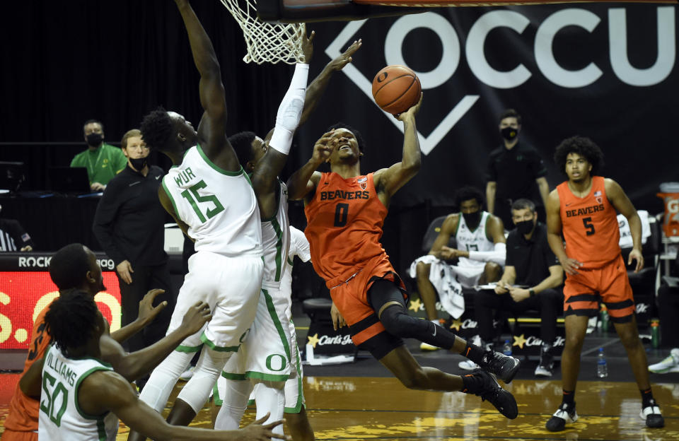 Oregon State guard Gianni Hunt (0) drives to the basket as Oregon forward Lok Wur (15) defends on the play during the first half of an NCAA college basketball game Saturday, Jan. 23, 2021, in Eugene, Ore. (AP Photo/Andy Nelson)
