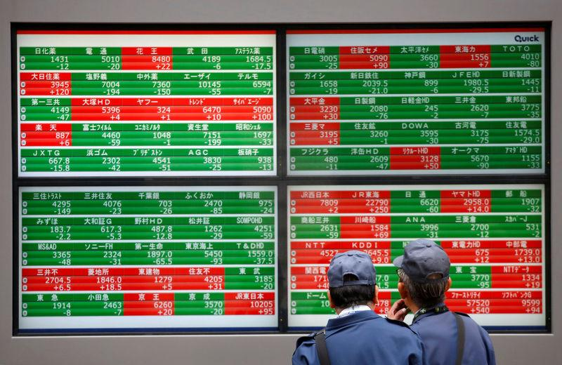FILE PHOTO: Men look at stock quotation boards outside a brokerage in Tokyo, Japan, December 5, 2018. REUTERS/Issei Kato