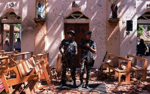 Sri Lankan military stand guard inside a church - Credit: Stringer/Reuters