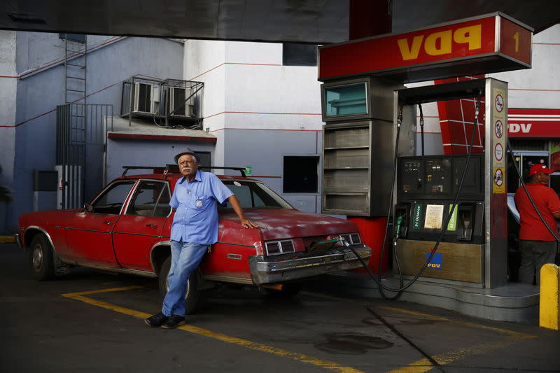 A man fills up his 1976 Chevy Nova with gasoline at a PDVSA gas station in Caracas