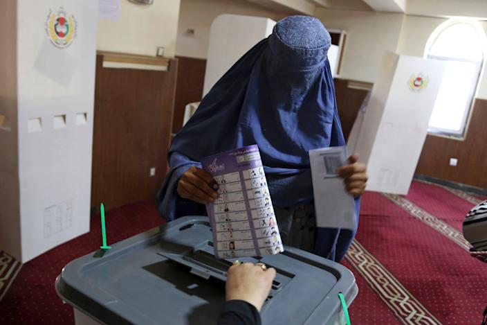 A woman casts his vote in Parliamentary elections in old city of Kabul, Afghanistan, Saturday, Oct. 20, 2018.