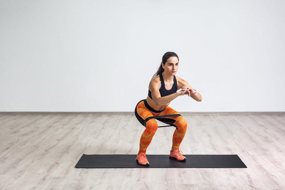 <ul> <li>Stand with your feet shoulder-width apart, your chest tall, and a booty band around your thighs.</li> <li>Hold your hands at chest level, and bend your knees to push your butt back into a squat like you're sitting on a chair, engaging your core.</li> <li>Push your thighs outward against the resistance band to maintain tension.</li> <li>Keep your chest lifted, and do not let your lower back round.</li> <li>Jump up explosively, swinging your arms backward as you do.</li> <li>When you land, lower your body back into the squat position to complete one rep. Make sure you land with your entire foot on the ground and with control.</li> <li>If these are too high-impact for you, try traditional squats instead.</li> </ul>