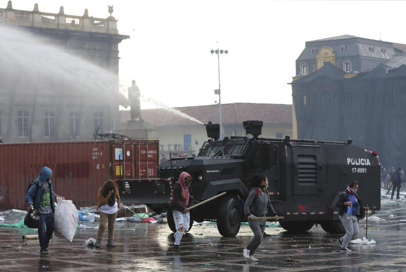 A police water cannon disperses anti-government protesters during a nationwide strike, at Bolivar square in downtown Bogota, Colombia, Thursday, Nov. 21, 2019. Colombia's main union groups and student activists called for a strike to protest the economic policies of Colombian President Ivan Duque government and a long list of grievances. (AP Photo/Fernando Vergara)