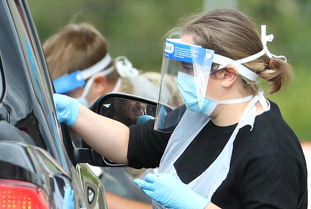 A medical worker wearing a protective face mask and screen, disposable gloves and a plastic apron, takes a swab at a coronavirus drive-through testing centre. (Getty Images)