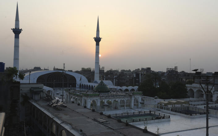 The sun sets through the shrine of a famous saint Ali Al-Hajweri known as Data Darbar, which is closed due to new restrictions announced by government to help control the spread of the coronavirus, in Lahore, Pakistan, Friday, Aug. 6, 2021. (AP Photo/K.M. Chaudhry)