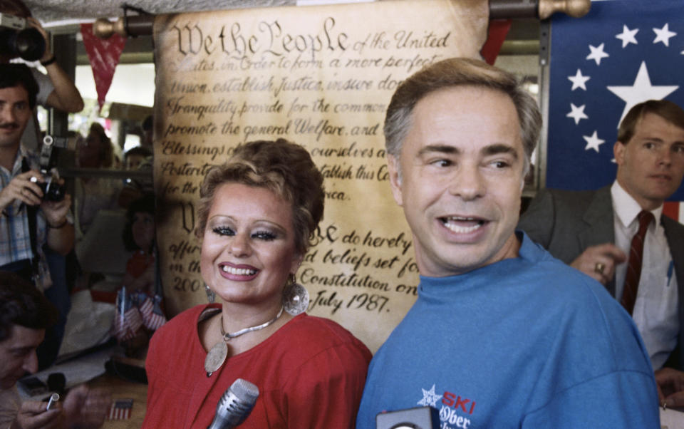(Original Caption) Gatlinburg, Tenn.: Jim Bakker, founder of the PTL television ministry and his wife Tammy Faye stand in front of a replica of the Constitution after signing a scroll to commemorate the bicentennial of the signing of the constitution.