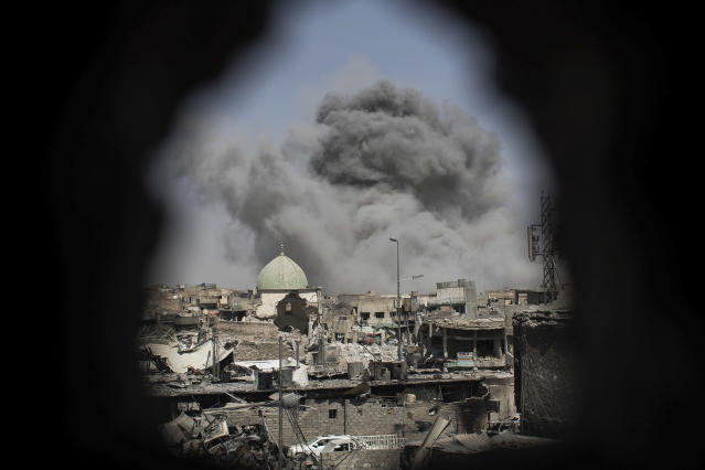 <p>A bomb explodes behind the al-Nuri mosque complex, as seen through a hole in the wall of a house, as Iraqi Special Forces move toward Islamic State militant positions in the Old City of Mosul, Iraq, Thursday, June 29, 2017. (Photo: Felipe Dana/AP) </p>
