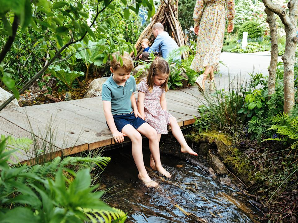 Prince George and Princess Charlotte dip their feet in the garden's pond during their first visit to the garden on Sunday [Photo: Matt Porteous]