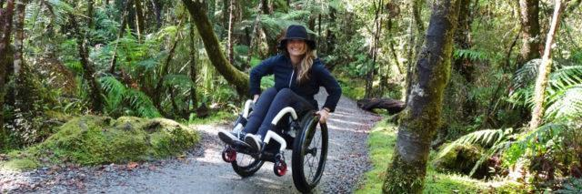 Ashley wheeling down a paved trail in the woods.