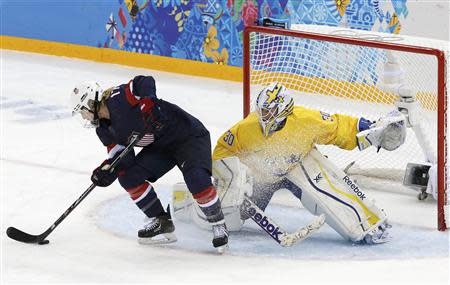 Team USA's Jocelyne Lamoureux (L) tries to spin around and score on a penalty shot against Sweden's goalie Kim Martin Hasson during the third period of their women's semi-final ice hockey game at the 2014 Sochi Winter Olympics, February 17, 2014. REUTERS/Grigory Dukor