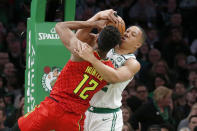 Boston Celtics forward Grant Williams and Atlanta Hawks forward De'Andre Hunter (12) vie for a rebound during the first half of an NBA basketball game Friday, Feb. 7, 2020, in Boston. (AP Photo/Mary Schwalm)
