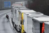 A driver walks next to lorries parked on the M20 motorway towards Eurotunnel and the Port of Dover