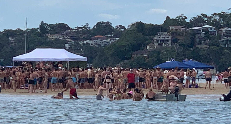 Dozens of people gather on a sandbar in Lilli Pilli to celebrate Australia Day, before the party was shut down by police.