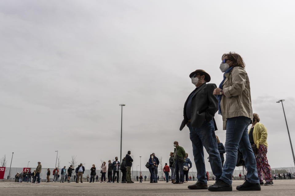 People queue to be vaccinated against COVID-19 at the Wanda Metropolitano stadium, Madrid, Spain, March 30, 2021. Spain is trying to stamp out a new wave of COVID-19 among its youth thanks to a robust vaccination program that is widely supported. Spain like the rest of the European Union got off to a slow start to compared to the United States and Britain when the first vaccines were released. But it has quickly made up ground once deliveries by drug makers started flowing. (AP Photo/Olmo Calvo)