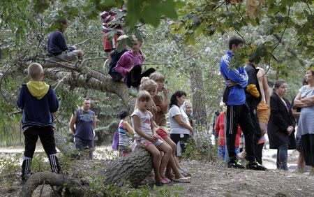 Ukrainian refugees from the Donetsk region wait to receive food as humanitarian aid on the outskirts of the southern coastal town of Mariupol September 10, 2014. REUTERS/Vasily Fedosenko
