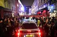 A car tries to drive along a street filled with revellers drinking in the Soho area of London (AFP Photo/JUSTIN TALLIS)