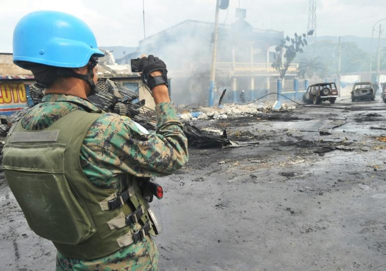 A UN peacekeeper inspects the aftermath of a 2013 blaze that swept through a market in Port-au-Prince