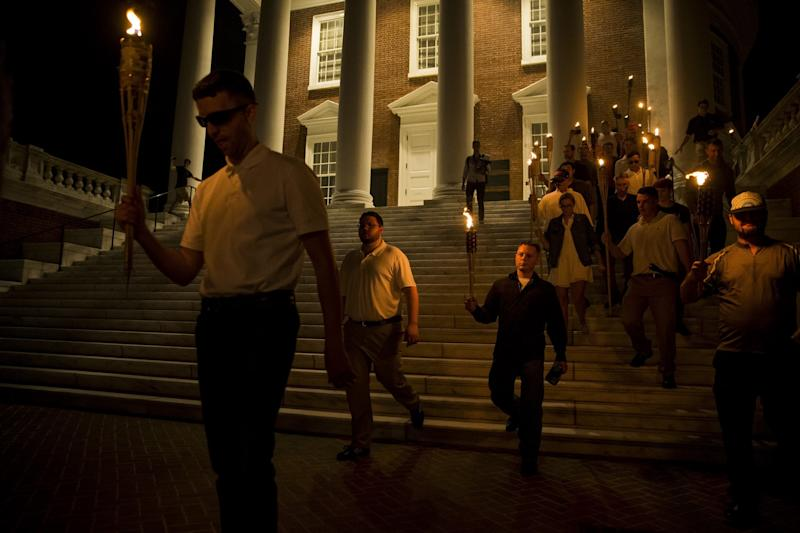 A white woman (right) walks down the steps witha group of neo-Nazis at the University of Virginiaon Aug. 11. (Anadolu Agency via Getty Images)