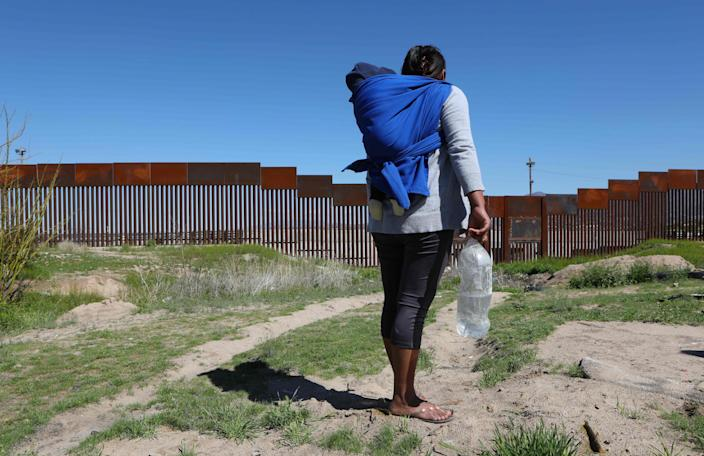 A migrant carrying a toddler stands in front of the border wall that divides Sunland Park, New Mexico, United States, with Ciudad Juarez, state of Chihuahua, Mexico on March 14, 2020.