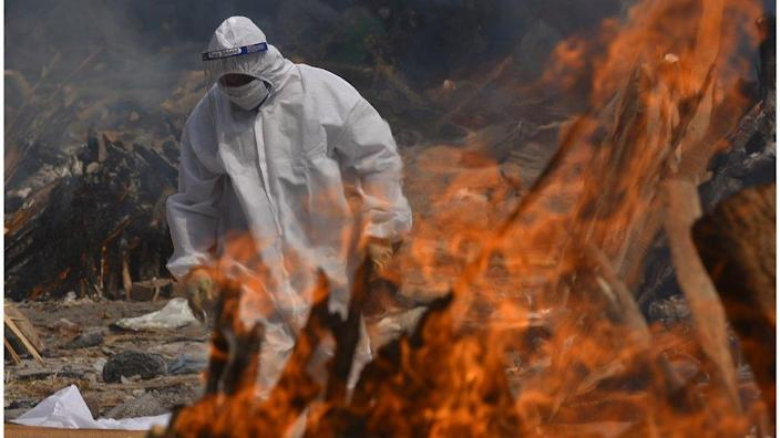 A Family member, wearing a Personal Protective Equipment (PPE), performs the last rites for COVID-19 victims