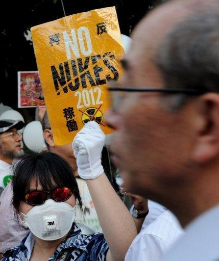 A protester displays a placard during an anti-nuclear protest in Tokyo on August 10. Japanese PM Yoshihiko Noda insists the country will go nuclear free as he rebutts criticism that his government is unable to come up with a coherent position on the issue